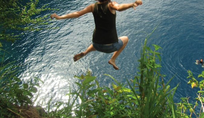 Girl traveler jumping off a cliff into Caribbean waters