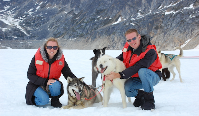 Traveling couple in the snow with some huskies