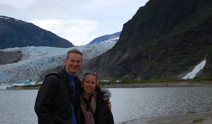 Cold couple standing in front of an iceberg and river overseas