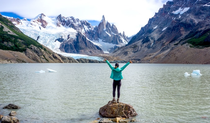 Kristin Addis stands on a stone in the waters of Cerro Torre in Patagonia