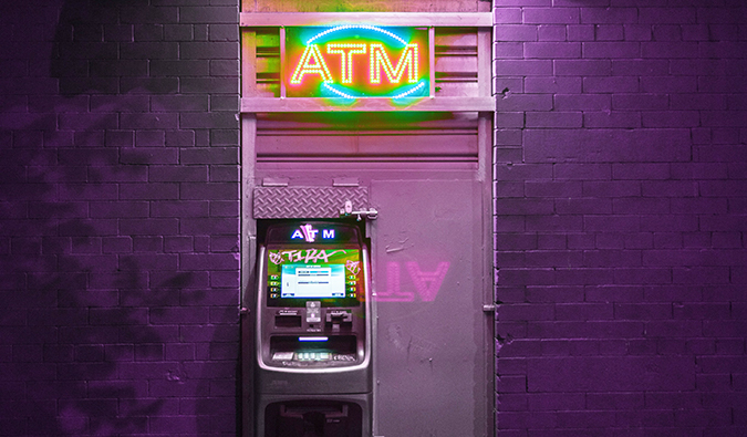 An ATM lit up at night against a purple brick wall