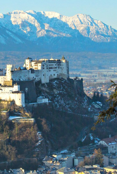 a historic castle in Salzburg with snowcapped mountains in the background