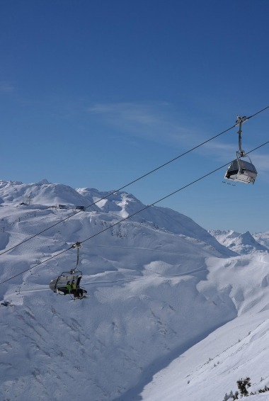 A ski lift in Arlberg taking skiiers up the mountain in Austria