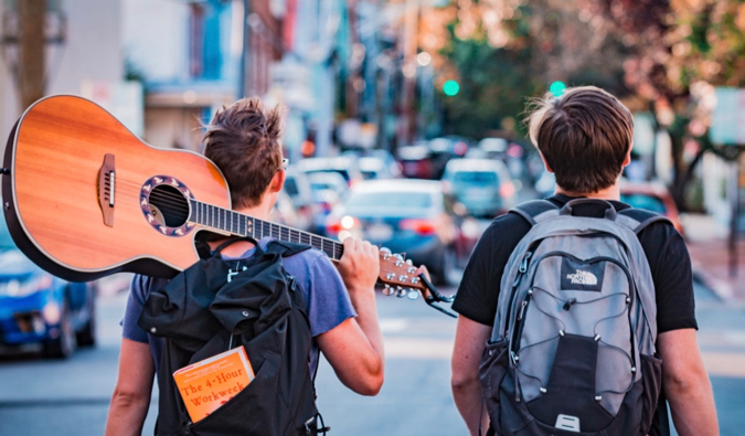 two backpackers with a guitar