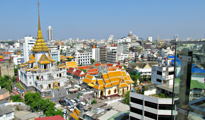 A dated picture of Bangkok's skyline, with a temple in the foreground