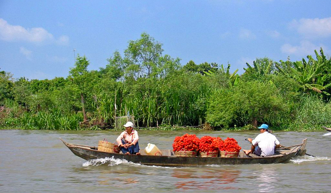 locals in boats on the Mekong River; Photo by Thomas Schoch; Wikimedia Commons