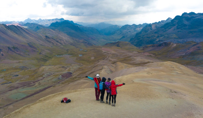 A group of solo female travelers hiking together in the mountains