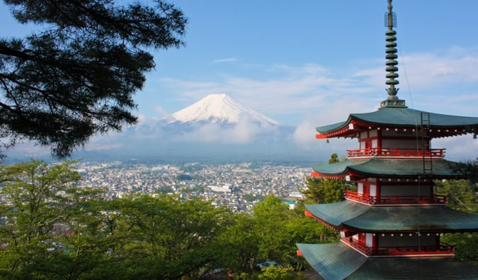 a tall, colorful Buddhist pagoda overlooking Mount Fuji in Japan