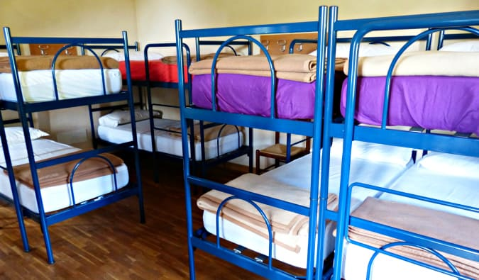 A hostel dorm room full of creaky blue metal bunk beds