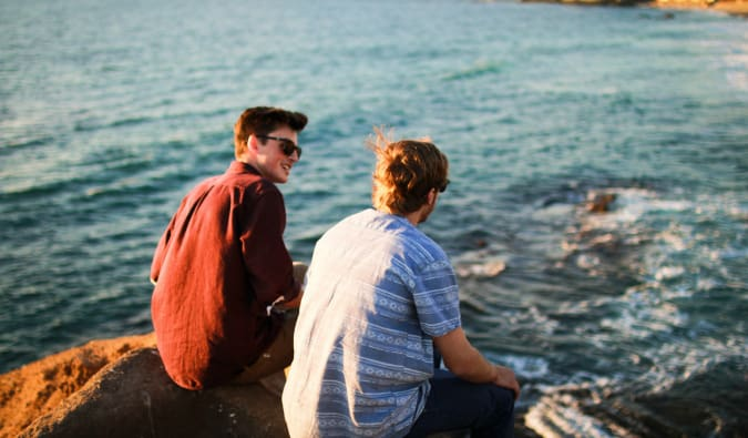 Two male travelers sitting by the water talking to each other