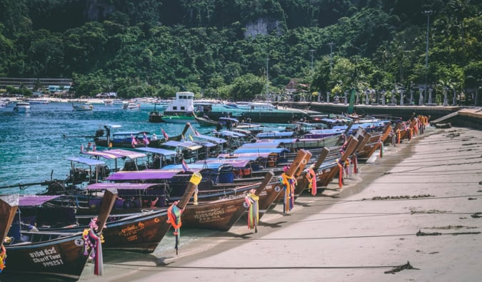 a crowded beach full of boats on Koh Phi Phi in Thailand