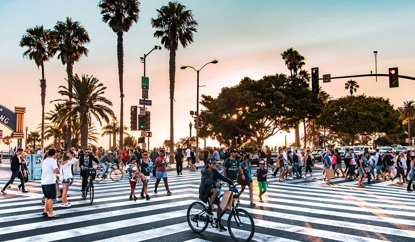 A busy Los Angeles crosswalk full of people during sunset