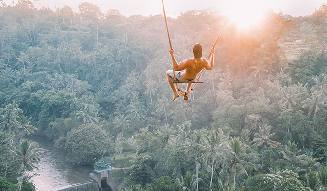 a man swinging in a jungle swing