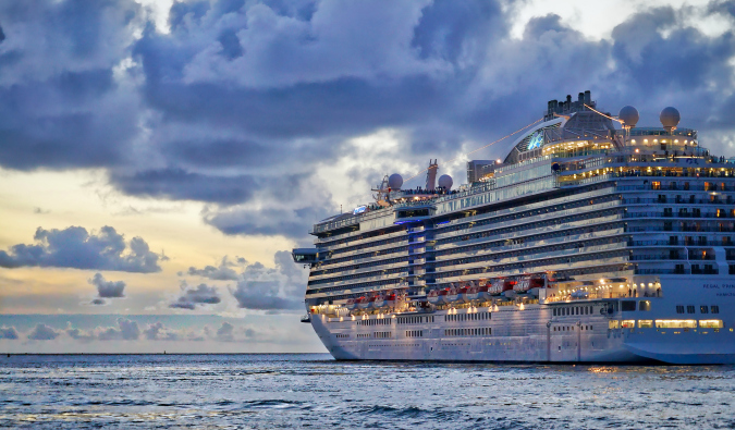 A large cruise ship sailing into a cloudy sunset