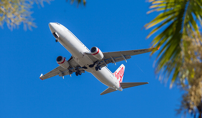 A Virgin Australia airplane flying against a bright blue sky