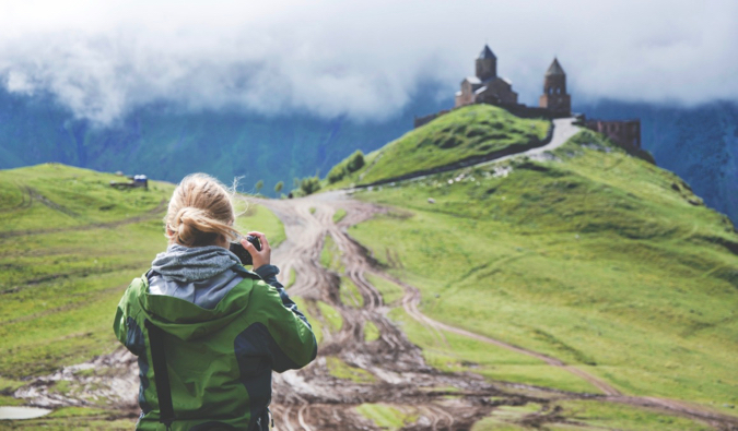 A solo traveler taking a photo of a castle on a hill
