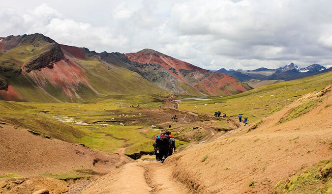 hikers walking through a trail on Rainbow Mountain