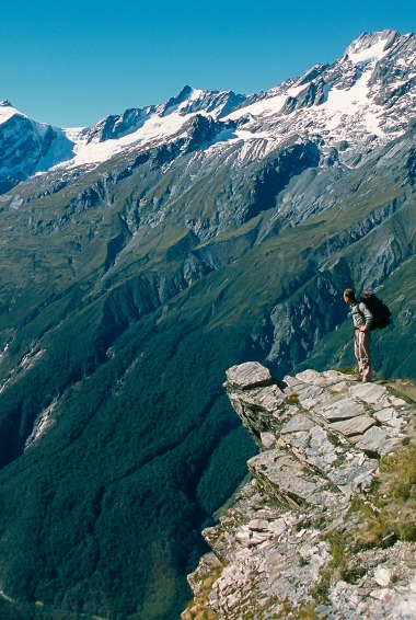 a hiker standing on the edge of a cliff close to Diamond Lake in New Zealand