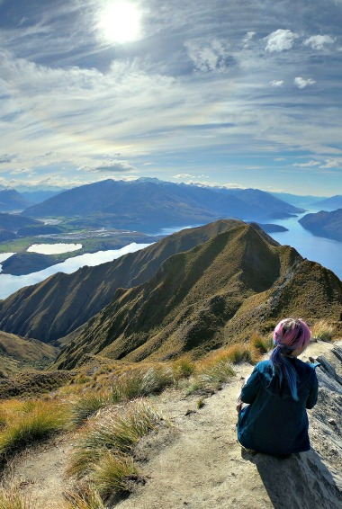 Woman sat enjoying the view at Roy's Peak in New Zealand. Photo by Alexandre Breveglieri (flickr:@breveglieri)