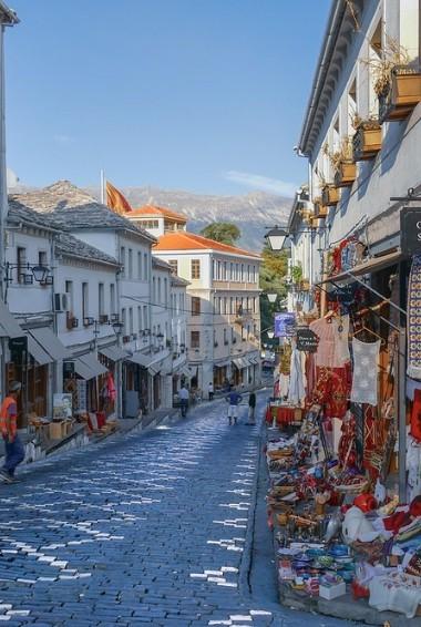 People walking down a cobbled street in Gjirokaster in Albania.