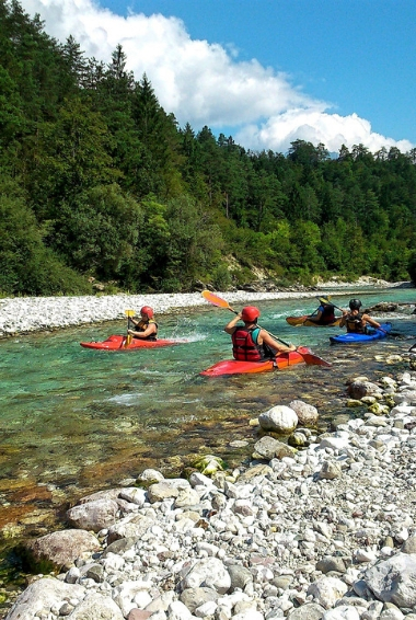 People kayaking in So?a on the river in the Slovenia forest