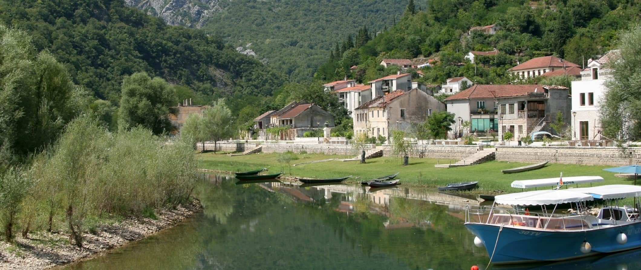A small village surrounded by trees on the banks of a river in Montenegro