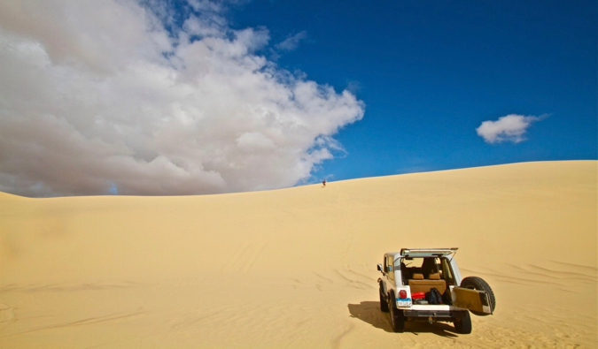 A rented car exploring the sand dunes in Africa under a bright blue sky