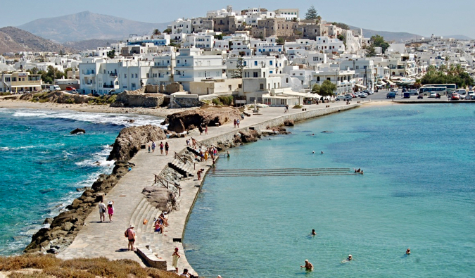 People swimming in the clear waters of Naxos, Greece