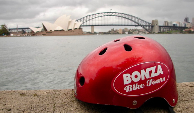 A red Bonza Bike Tour helmet sitting on the cement near the water in Sydney, Australia
