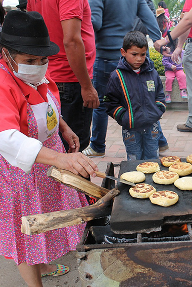 a woman cooking street food in Colombia