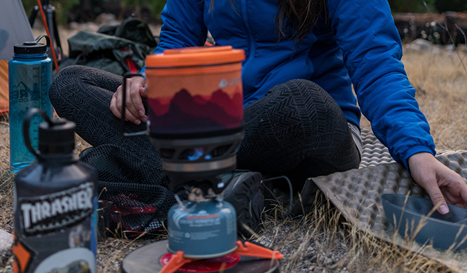 a woman setting up a campfire while camping