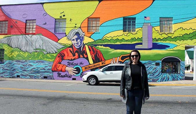 Caroline Eubanks standing in front of a mural for Doc Watson in Wilkesboro, North Carolina