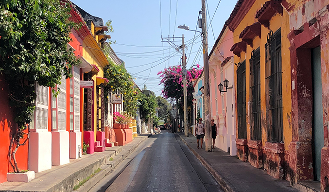 Brightly painted buildings along a narrow, empty street in Cartagena, Colombia