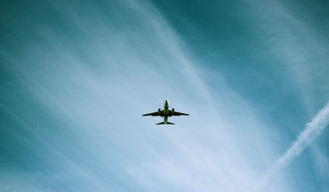 a commercial airplane flying agaisnt a clear blue sky