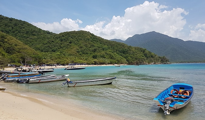 boats pulled up on a sandy beach in Tayrona National Park