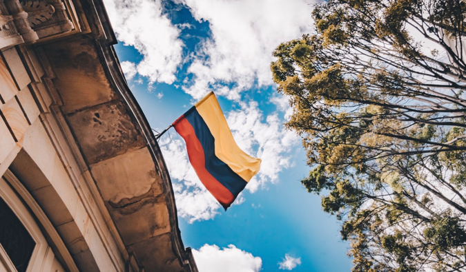 The flag of Colombia blowing in the wid as it hangs from a building