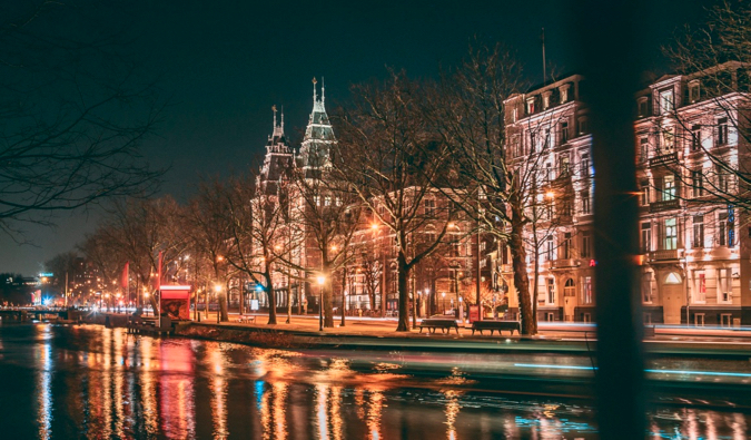 The busy streets and old buildings of Amsterdam at night