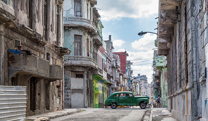 a green car driving by on a street in Havana