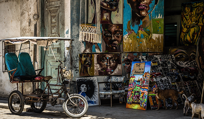 a bicycle parked outside an art shop in Cuba