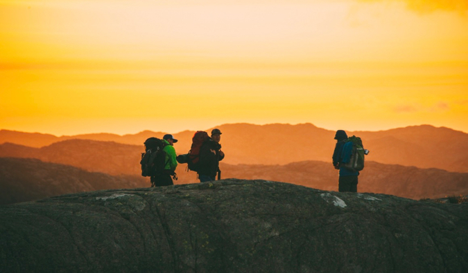 a group of travelers hiking at sunset in Norway