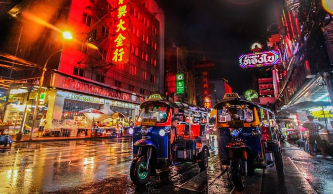 An up-close shot of the tuk-tuks in Bangkok, surrounded by bright neon lights at night