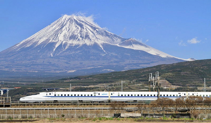 A super fast bullet train rocketing past a snow-capped Mount Fuji in Japan