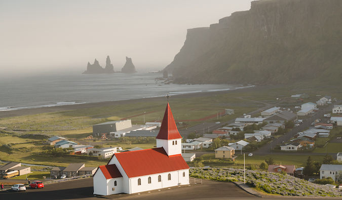 a red roof church in front of a black sand beach in Iceland