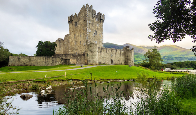 an Irish castle tower on a still lake set against green hills