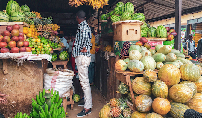 a man in Rwanda standing in a supermarket surrounded by fresh fruit