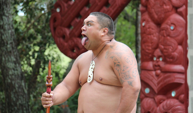 A large Maori warrior holding a spear while performing in New Zealand