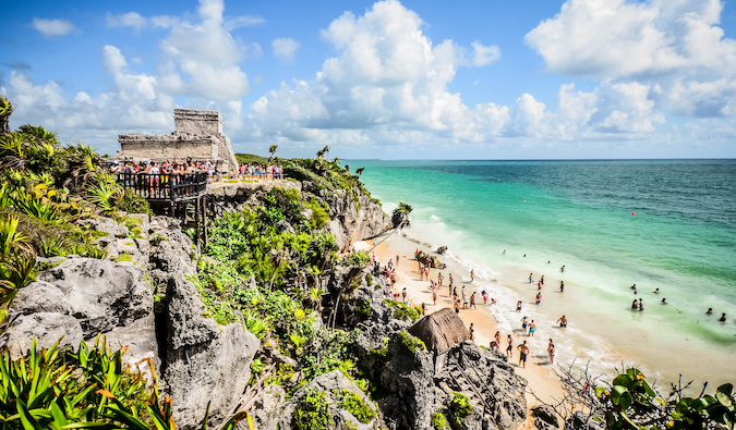 The Observatory ruins at Tulum, Mexico with people hanging out on the beach in front of it