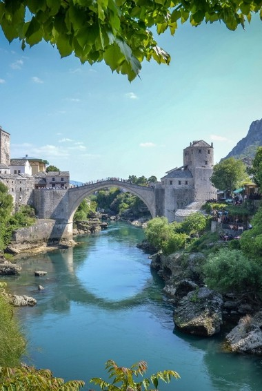 a view of a bridge over water with the town of Mostar in the background.