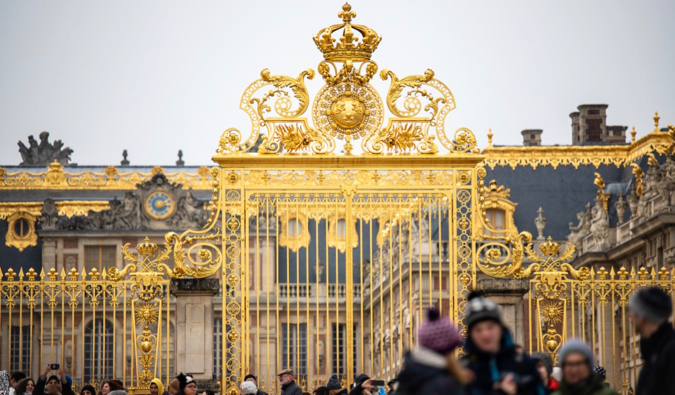 The ornate golden gates of the Palace of Versailles near Paris, France surrounded by tourists