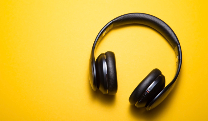 A pair of headphones on a bright orange background